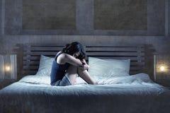 Das deprimierte lateinische Mädchen, das auf dem Bett durchdacht und besorgt ist über Problem sitzt oder krank und im Druck und i Stockbilder