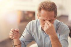 Das deprimierte reife Mannglauben ermüdete im Büro Stockfoto