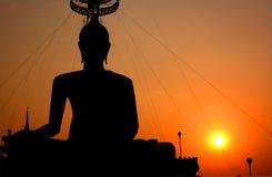 Das des Buddhas Schattenbild, das den Sonnenuntergang schneidet Stockfotos