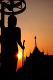 Das des Buddhas Schattenbild, das den Sonnenuntergang schneidet Lizenzfreie Stockfotos