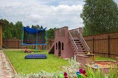 Das Dia, die Trampoline und der Sandkasten der Kinder auf dem Spielplatz Stockfotografie