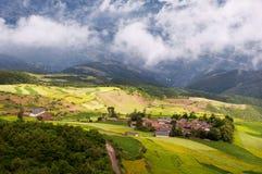 Das Dorf im Sonnenschein und in der Wolke Stockbild