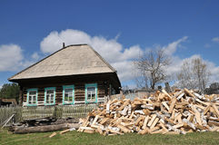 Das Dorfleben brach Birkenbrennholz am Tor des alten Holzhauses ab Stockfotos