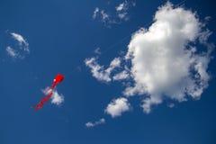 Das Drachenfliegen in Form von Kalmar fliegt hoch in den Himmel zwischen die Wolken stockfotografie