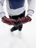 Das Draufsichtmädchen, das Rochen trägt, zeigt abstraktes Herzsymbol durch Lederhandschuhe auf Eis Konzept der Liebe zum Eislauf, Stockfoto