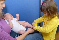 Das dreijährige Mädchen kleidet Babyschuhe auf Füßen zum Baby clo Stockfotografie