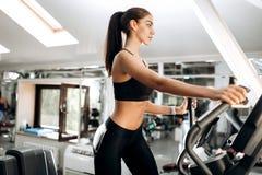 Das dunkelhaarige athletische Mädchen, das in der schwarzer Sportspitze und -strumpfhosen gekleidet wird, arbeitet auf einer Tret stockbilder