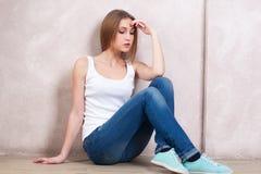 Das durchdachte Mädchen sitzt auf einem Boden nahe einer weißen Wand Lizenzfreies Stockfoto
