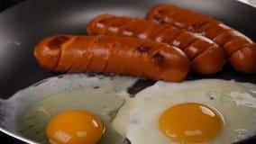 Das Ei fällt auf eine heiße Bratpfanne mit Würsten stock video