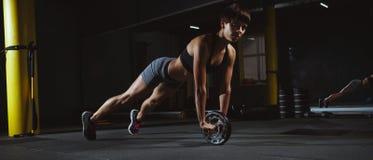 Das Eignungsmädchen, das crossfit Übungen in der Turnhalle mit tut, drehen herein Dunkelheit Lizenzfreie Stockfotos