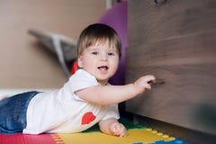 Das einjährige Kind öffnet die Fächer oder den Wandschrank Glückliches Baby liegt auf Boden Kind-` s an Raum und an Spielen lizenzfreie stockbilder