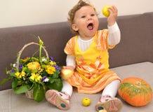 Das einjährige Mädchen sitzt auf einem Sofa, hält Äpfel in der Hand und lacht laut Lizenzfreies Stockfoto