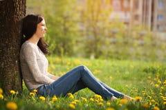 Das einsame Mädchen sitzt an den Blicken eines Baums in einem Abstand Lizenzfreies Stockbild