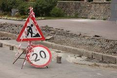 Das einschränkende Zeichen auf den Bürgersteig Reparaturen und die Zeichen Höchstgeschwindigkeit innerhalb 20 km/h sind gegenüber Lizenzfreie Stockfotos