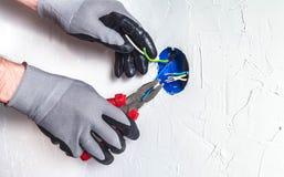 Das electrician& x27; s-Hände mit pasatises säubern die Drähte in einem Anschlusskasten Lizenzfreie Stockbilder