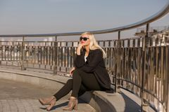 Das elegante blonde Modell, das im schwarzen Mantel aufwirft, trägt Sonnenbrille auf a Lizenzfreie Stockfotos
