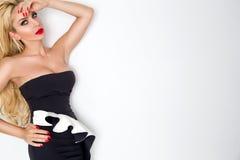 Das elegante erstaunliche blonde weibliche Modell, das auf einem weißen Hintergrund steht, kleidete im eleganten Schwarzweiss-Kle Lizenzfreies Stockfoto
