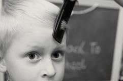 Das Elternteil kämmt ihren Jungen mit einem traurigen Gesicht vor der Schule Stockfotografie