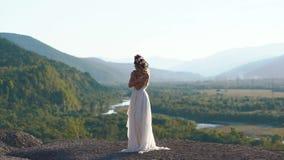 Das empfindliche Porträt der Schönheit im weißen langen boho Kleid und im Kranz von Blumen auf ihrem Kopf an stock video