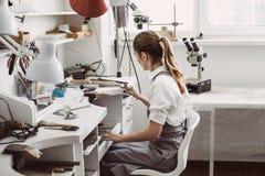 Das Ende des Arbeitstages Seitenansicht des jungen weiblichen Juweliers, der an ihrer Schmuckwerkstatt sitzt und ihren Arbeitspla lizenzfreies stockfoto
