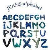 Das englische Alphabet wird von den Buchstaben ausgebreitet, die aus Jeanskleidung des verschiedenen Schattens bestehen stockfotos