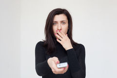 Das entsetzte Mädchen schaltet das Programm im Fernsehen Lizenzfreies Stockfoto
