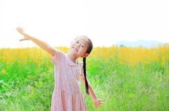 Das entzückende kleine asiatische Kindermädchen, das sich frei mit fühlt, entspannen sich breites offenes der Arme auf dem Sunnha lizenzfreie stockbilder