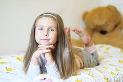 Das entzückende kleine Mädchen, welches die Kamera mit seinen Armen betrachtet, kreuzte hinter ihrer Hauptnahaufnahme lizenzfreie stockfotografie