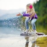 Das entzückende Mädchen, das durch Hallstatter spielt, sehen See in Österreich am warmen Sommertag Nettes Kind, das Spaßspritzwas lizenzfreies stockbild