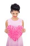 Das erfreute Modell des schwarzen Haares, das ein rosa Herz hält, formte Kissen Stockfoto