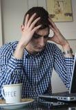 Das ernste junge Geschäftsmannschauen sorgte sich im Büro des Laptopschirmes zu Hause Lizenzfreie Stockbilder