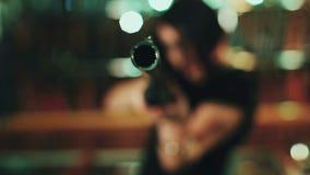 Das erschrockene Mädchen, zum auf die Kamera mit einem Gewehr zu zielen Das erschrockene Mädchen, zum auf die Kamera mit einem Ge stock video