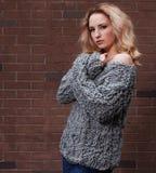Das erstaunliche langhaarige blonde Mädchen, das in einem Grau aufwirft, strickte Strickjacke und Jeans in der Straße auf einem H Lizenzfreie Stockfotografie