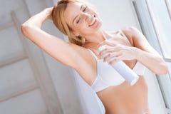 Das erstaunliche Mädchen, das desodorierendes Mittel kastrieren verwendet herein Lizenzfreie Stockfotografie
