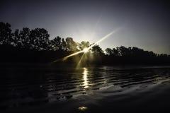 Das erste Licht des Tages - das Licht vom Sonnenglanz durch die Bäume morgens am Strand stockfotos
