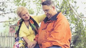 Das erwachsene Paar, das in einem Park auf einer Bank, eine Frau justiert sitzt sorgfältig, Haar auf ihren Ehemann Langsame Beweg stock video footage