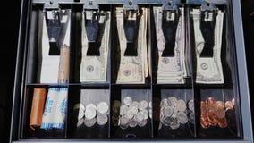 Das Fach des Bargeldschreibtisches öffnet sich, wo Bargeld US-Dollars und Münzen liegen Ansicht von oben stock video