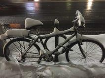 Das Fahrrad, das auf verkehrsreicher Straße im Schnee geparkt wurde, bedeckte Stadt nachts Stockfoto