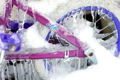 Das Fahrrad der rosa und blaue Kinder bedeckt im Eis Stockfotos