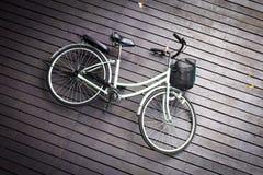 Das Fahrrad stieß auf dem braunen Bretterboden, Draufsicht des Fahrrades auf Gehweg zusammen lizenzfreie stockbilder
