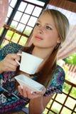 Das fair-haired Mädchen hält ein weißes Cup in den Händen an stockbilder