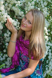 Das fair-haired Mädchen sitzt in einem Garten lizenzfreie stockbilder