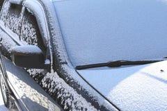 Das Fenster des Autos mit Schnee und der Wischer an einem sonnigen Tag im Winter Lizenzfreie Stockbilder