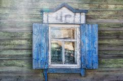 Das Fenster mit dem hölzernen geschnitzten Architrav im alten Holzhaus in der alten russischen Stadt stockfotografie