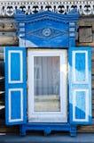 Das Fenster mit dem hölzernen geschnitzten Architrav im alten Holzhaus in der alten russischen Stadt lizenzfreie stockfotografie