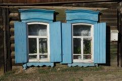 Das Fenster mit dem hölzernen geschnitzten Architrav im alten Holzhaus in der alten russischen Stadt stockfoto