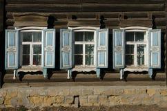 Das Fenster mit dem hölzernen geschnitzten Architrav im alten Holzhaus in der alten russischen Stadt lizenzfreies stockbild