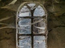 Das Fenster mit Spinnennetzen eines alten Bauernhauses Lizenzfreies Stockfoto