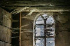 Das Fenster mit Spinnennetzen eines alten Bauernhauses Stockfoto