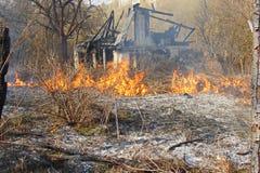 Das Feuer auf dem Hintergrund des gebrannten Hauses Stockfoto